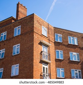 Block of council flats in red bricks and white windows