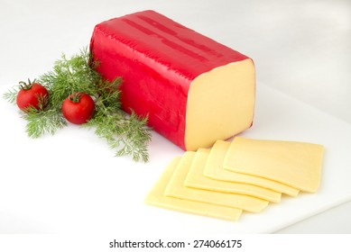 A block of edam cheese with slices on white background.