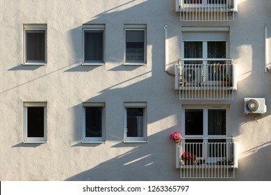 Block of flats facade in the morning sun with air conditioning units fitted on the wall, some blooming plants on small balconies in Budapest, Hungary. Long shadows on the wall.