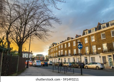 Block of flats at sunset in london and many cars stopped at the red light during the rush hour.