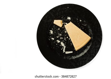 Block of fresh parmesan cheese on a black plate