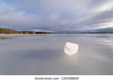 Block of ice on frozen lake landscape