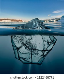 block of ice with underwater view and greenland background
