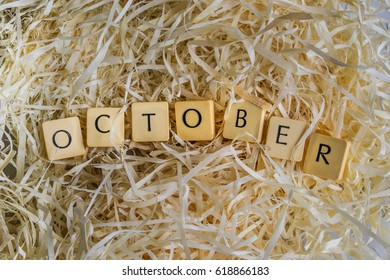 """Block Letters of the month """"October"""" word on wood shavings"""