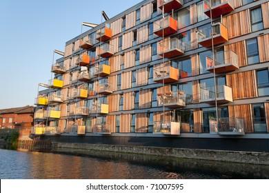 A block of modern apartment building alongside Regent's Canal (London) under warm sunset light