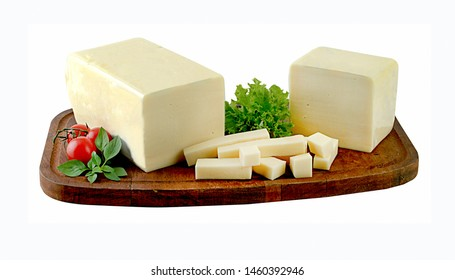Block of mozzarella cheese and pieces on wooden board.