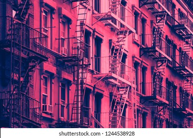 Block of old New York City buildings in pink and blue