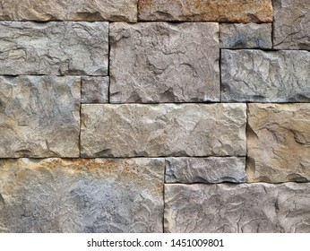 Block shaped stone wall made of rocks with different geometric shapes.  Detail, background and texture