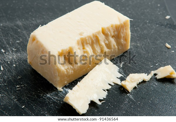 a block of sharp white cheddar cheese, some cut in front on a white background and black cutting board