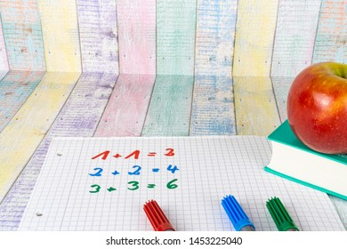 A block with simple calculating tasks and an apple fruit, colorful wood background and copy space