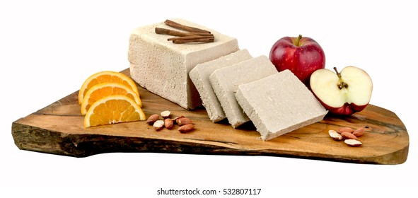 A block of traditional Greek vanilla halva with pieces on wooden board.Clipping path.