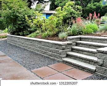 Block wall capture of a concrete block retaining wall with steps incorporated into an existing garden landscape with a professional design stepping stones concrete pad lush foliage perennial flowers
