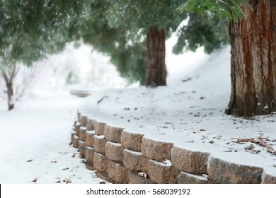 A block wall leads to infinity in the snow with pine trees.  Perfect for the background for a portrait studio photographer.