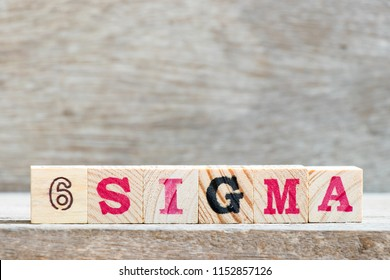 Block in word 6 sigma on wood background