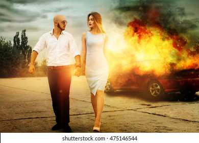 blockbuster picture as a man and a woman go away from burning car outdoors and looking at each others