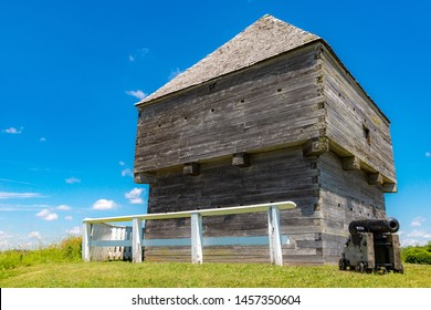 The blockhouse at Fort Howe in Saint John, New Brunswick, Canada. A cannon is on the grass next to the blockhouse, and the sky is blue above. Sunny day.