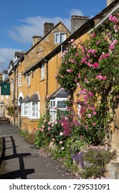BLOCKLEY, GLOUCESTERSHIRE, ENGLAND - JUNE 03, 2017: Rose covered frontage of honey colored Cotswold stone cottages along the High Street with blue sky