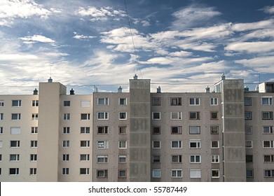 blocks of flats against blue cloudy sky