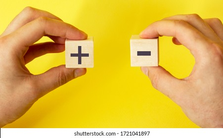 blocks in hands on a yellow background with plus and minus