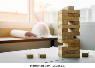 the blocks wood tower game with architectural engineer plans or blue prints compasses ,pencils and ruler on wooden table, plan and building concept.