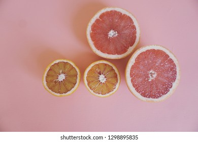 Blod orange and grape fruit on coral colored background