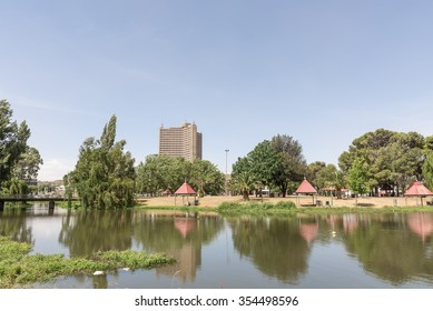 BLOEMFONTEIN, SOUTH AFRICA, DECEMBER 21, 2015: Picnic places on Loch Logan Island with a high-rise apartment building in the back