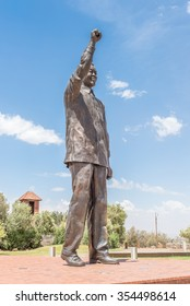 BLOEMFONTEIN, SOUTH AFRICA, DECEMBER 21, 2015: The 6.5m bronze statue of Nelson Mandela on Naval hill in Bloemfontein with part of the historic powder magazine visible in the back