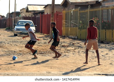 """Bloemfontein / South Africa - March 13th 2019: Black children from a suburb playing soccer in a street"""