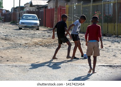 """Bloemfontein / South Africa - March 13th 2019: Black children from a suburb playing soccer - street photograpy"""