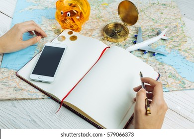 Bloger planning budget of trip Hands holding pen near notebook Table with traveling theme items mobile phone, map, compass, plane and piggy bank Empty mockup notes, your can place text logo images.