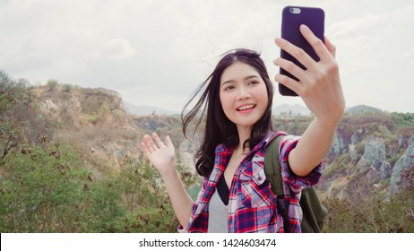Blogger Asian backpacker woman record vlog video on top of mountain, young female happy using mobile phone make vlog video enjoy holidays on hiking adventure. Lifestyle women travel and relax concept.