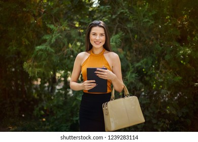blogger, businesswoman with tablet and bag in hands on nature