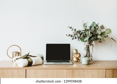 Blogger, freelance home office desk workspace. Laptop with mock up screen on wooden desktop decorated with eucalyptus bouquet, gift box, candles on white background. Blog, website hero header.