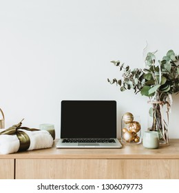 Blogger, freelance home office desk workspace. Laptop with mock up screen on wooden desktop decorated with eucalyptus bouquet, gift box, candles on white background.