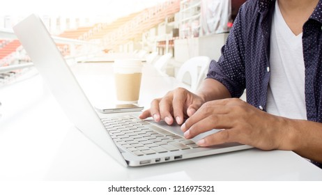Blogger freelancer is working Using laptop computer in home office, Blogger writes Articles presenting football league information on sport web site online .