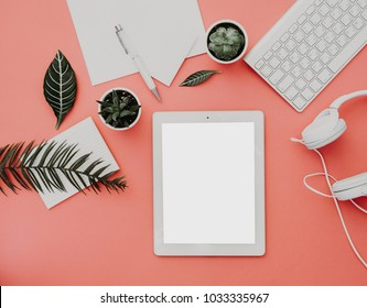 Blogger or freelancer workspace with tablet, headphones and accessories on pastel background. Mock up, Flat lay, top view, minimalistic  styled home office desk. Blog concept.