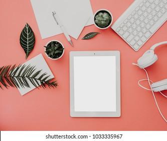 Blogger- oder Freelancer-Arbeitsbereich mit Tablette, Kopfhörer und Zubehör auf pastellfarbenem Hintergrund. Mock up, Flat lay, Draufsicht, minimalistischer Schreibtisch für die Wohnung. Blog-Konzept.