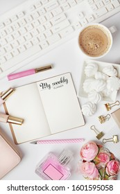 blogger or freelancer workspace with weekly planner, notebook, laptop, coffee and female fashion accessories on white background. Flat lay, top view office table desk.