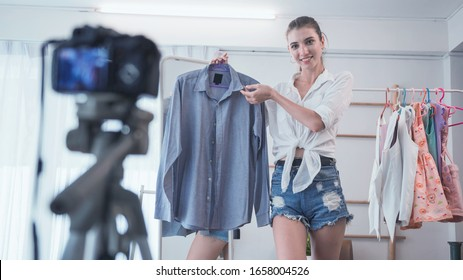 Blogger girl review product and talking camera live recording video on social network at home. Online selling clothes on social media.