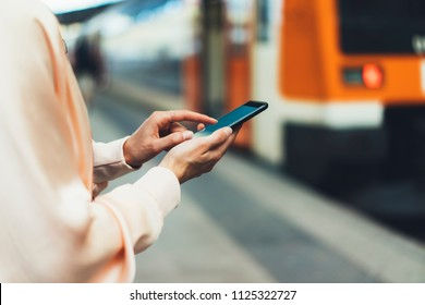blogger hipster using in hands gadget mobile phone, woman texting message on blank screen smartphone, mockup online wifi internet concept, hipster waiting on station platform on background train