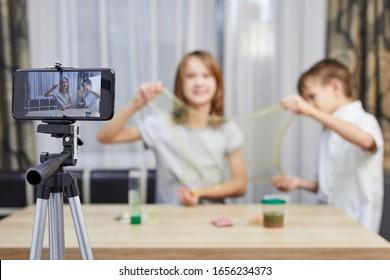 Blogger kid posing for recording homemade video to vlog. Children make vlog about slime for social media channel.