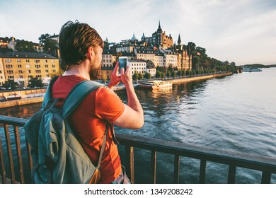 Blogger man taking photo by smartphone of Stockholm city view travel lifestyle summer vacations in Sweden