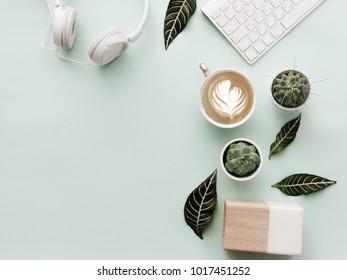 Blogger-Pastellhintergrund mit Kaffee-Cup, Kopfhörern und botanischen Elementen. Flach-Lay