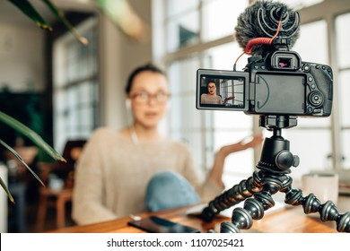 Blogger recording content for her blog on a camera mounted on flexible tripod. Woman wearing earphones video recording content for her blog sitting at home.