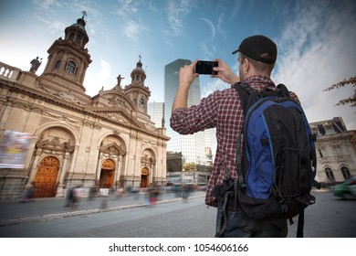 blogger shoots a video about traveling on the background of the Plaza de las Armas square in Santiago, Chile