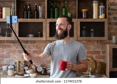 blogger streaming live video using mobile phone camera and selfie stick. bearded hipster man communicating with subscribers from his kitchen.