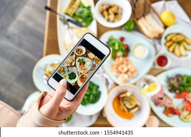 A blogger takes a photo on a smartphone for social networks. Table with Plates seafood BBQ with garnish. Variety of dishes on the table. Restaurant menu.