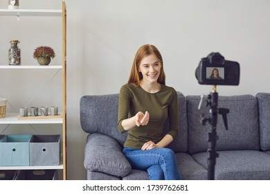 Blogger vlogger girl speaks to the camera while sitting on a sofa in a room at home.