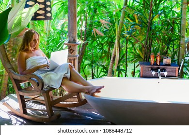 Blogger work freelance on laptop computer, type text for travel blog sitting at rocking chair. Relaxing woman fill bath tub in Boho chic style bathroom at veranda in luxury villa on tropical island