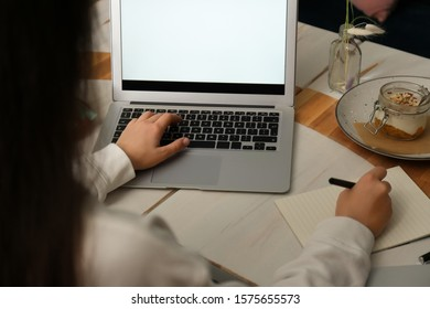 Blogger working with laptop in cafe, closeup